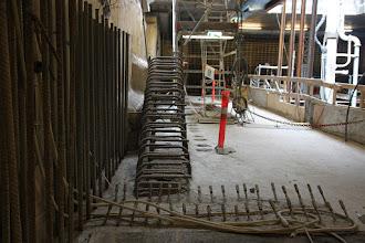 Photo: På Concoursen, hvor der bliver billetautomater og adgang fra trapper i to sider. En af trapperne skal ned ved A4 flugtvejsskiltet. Den inderste væg støbes nedefra, så heroppe er kun armeringsjernet gjort klar.