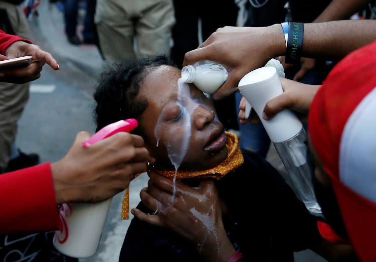 A woman affected by pepper spray is attended to by others during a protest amid nationwide unrest following the death in Minneapolis police custody of George Floyd, at Lafayette Park near the White House in the US capital.
