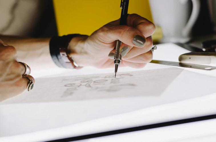 Logo de arquitetura: pessoa desenhando com lapiseira os contornos de um logotipo.