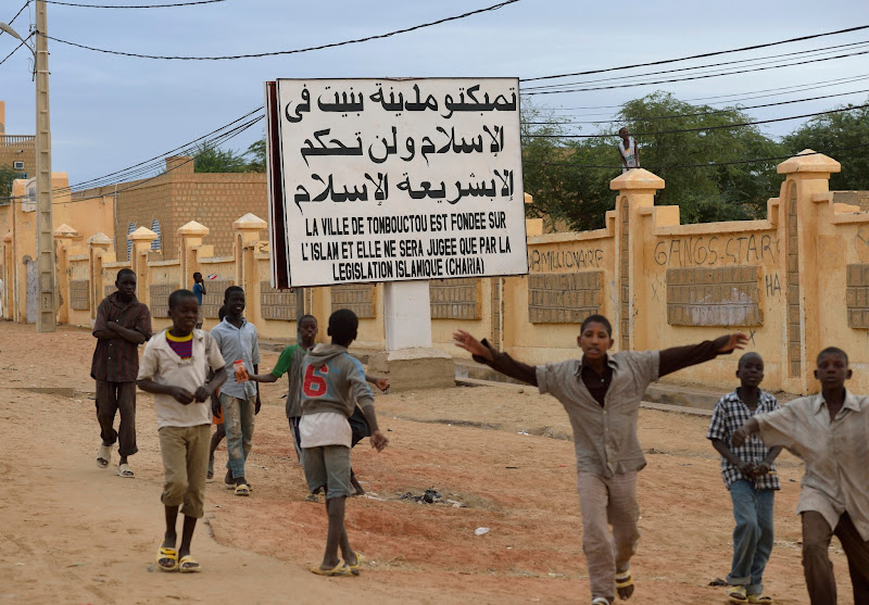 """Photo: Children wave after Malian and French soldiers entered the historic city of Timbuktu, occupied for 10 months by Islamists who imposed a harsh form of sharia, on January 28, 2013. Hundreds of people scrambled Monday to give French-led troops a hero's welcome as they entered the city. Sings reads """"The city of Timbuktu is founded on Islam and will be judged only by the Islamic law.""""         AFP PHOTO ERIC FEFERBERG        (Photo credit should read ERIC FEFERBERG/AFP/Getty Images)"""