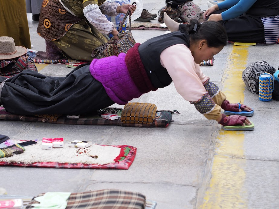 Pilgrims performing prostrations outside Jokhang Temple, Lhasa