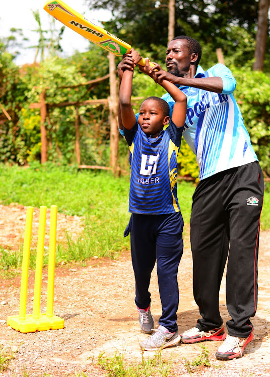 Former Kenyan international Jimmy Kamande takes upcoming cricketer Michael Ouma through a batting session at Kasarani.