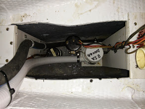 Photo: looking down into lower bilge with lower bilge pump float switch & hose on left and middle bilge pump & float switch on right