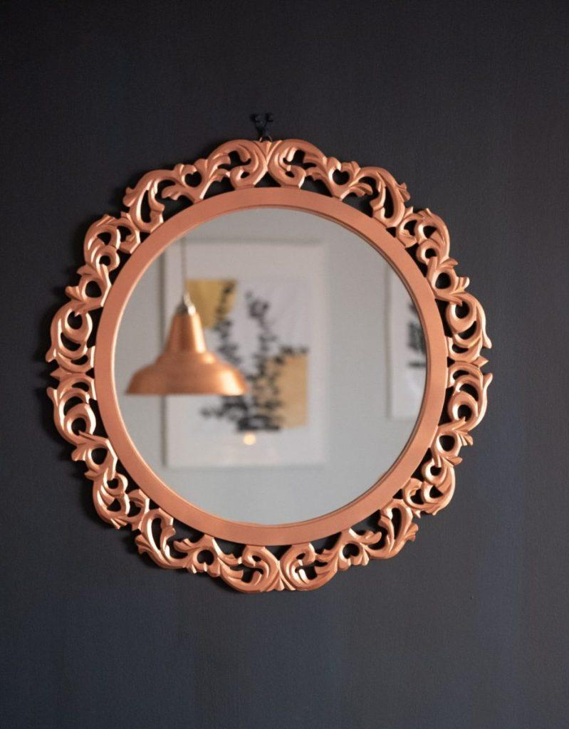 A round mirror on a black wall.
