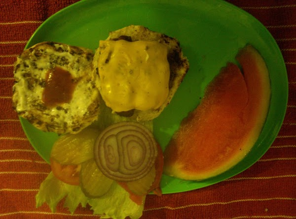 Place cheeseburger on bun add miracle whip, ketchup, onion tomatoes, lettuce and pickle. Serve...
