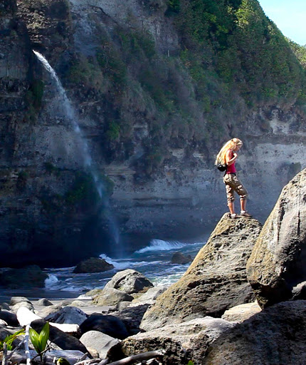 A hiker and waterfall at Wavine Cyrique in Dominica.