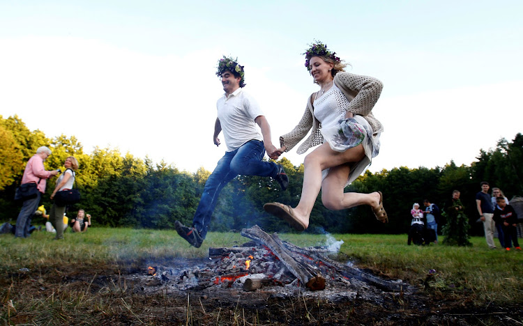 Belarusian people jump over a campfire as they take part in the Ivan Kupala festival in Belarusian state museum of folk architecture and rural lifestyle near the village Aziarco.