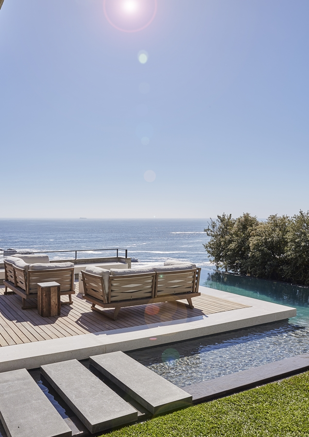 The L-shaped rim-flow pool creates a seamless connection between the garden and the ocean beyond.