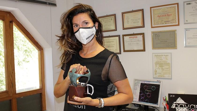 Rosalía Navarro, gerente de la agencia de modelos Navarro Pasarela, muestra su Premio de la ONCE.