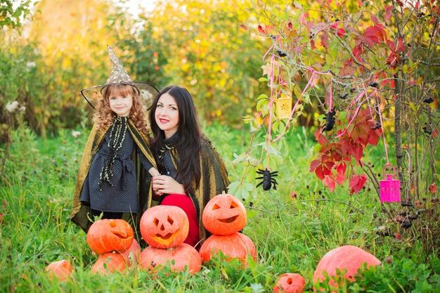 Mother and daughter with pumpkins dressed as witches outdoor Premium Photo