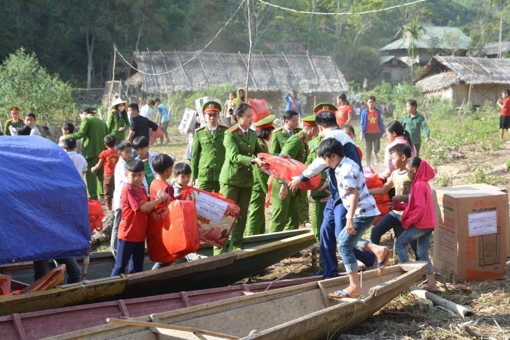 Đoàn thiện nguyện cùng các em học sinh vận chuyển quà từ thuyền lên trường THCS Hữu Khuông