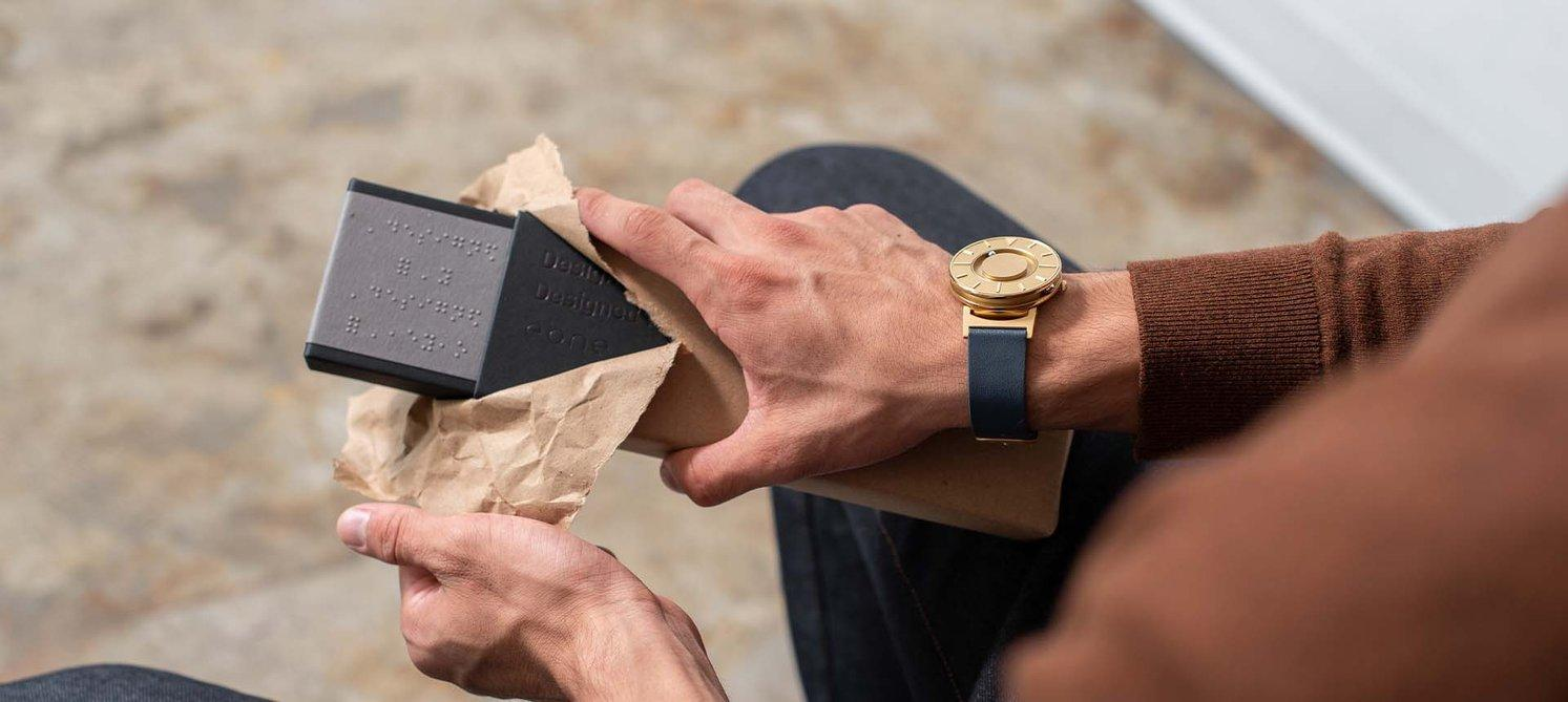 A guy with the golden Eone watch on his wrist unwrapping a package