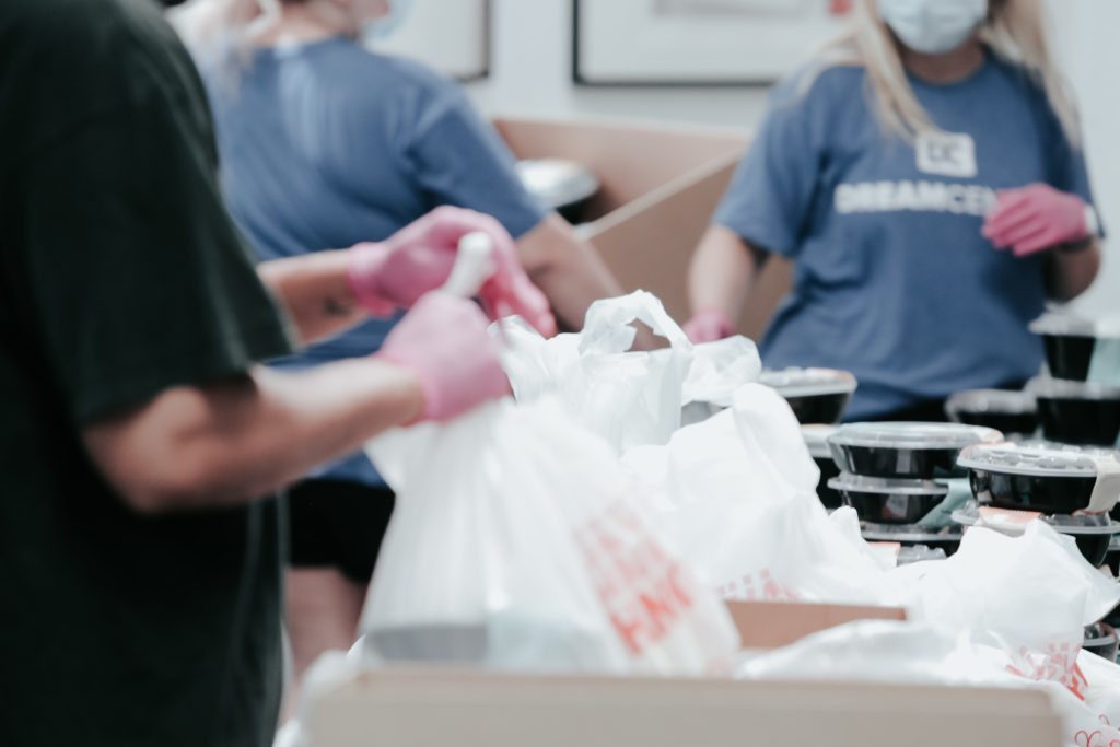 Image shows gloved hands bagging goods in a plastic bag as part of an employee volunteering initiative.