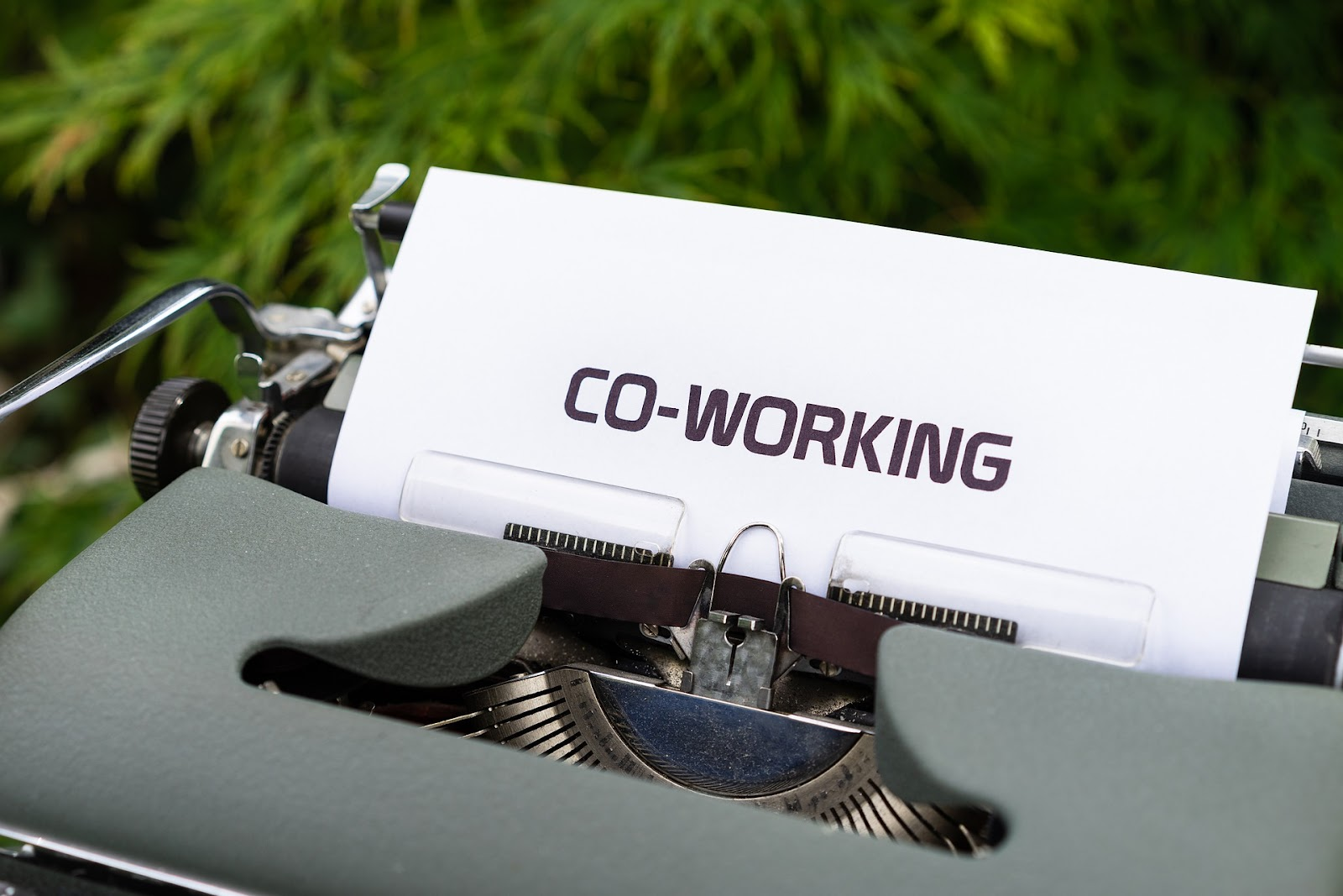 A typewriter with a sheet of paper that says, 'Co-working.'
