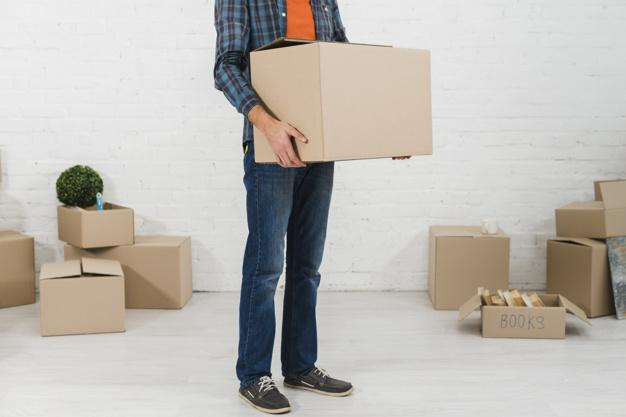Low section of a man holding cardboard box in his hand Free Photo