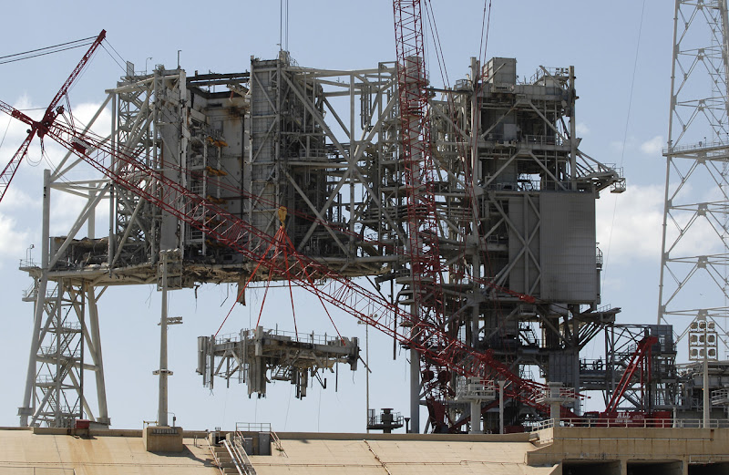 "Photo: A large crane dismantles a section of the fixed service structure on Launch Pad 39B at NASA's Kennedy Space Center in Florida, on April 6, 2011. The structure was designed to support the unique needs of the Space Shuttle Program. the pad is now being restructured for future use. Its new design will feature a ""clean pad"" for rockets to come with their own launcher, making it more versatile for a number of vehicles. (NASA/Kim Shiflett) - Via In Focus: http://theatln.tc/GXlgMp"