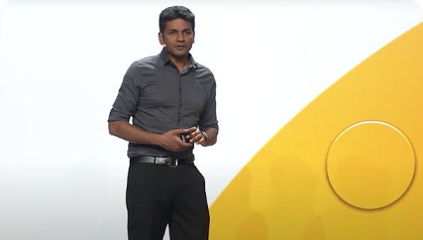 Un hombre con pantalones negros y una camisa gris realiza una presentación en el escenario