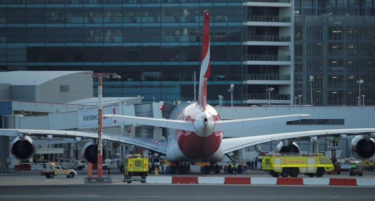 Fire engines position alongside a Qantas A380 aircraft after the Dallas-bound flight QF7 was forced to return and make an emergency landing due to mechanical fault at Sydney International Airport in Australia August 4, 2017.