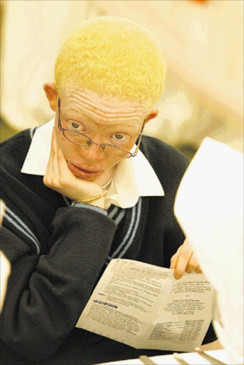 Karabo Takalo19, read papers while waiting for the function to start,  at the function organized by Albinism Society of South Africa (ASSA), held at Seanamarena Secondary School in Mapetla East Soweto. PIC. Sydney Seshibedi. 16/03/2006. © THE TIMES
