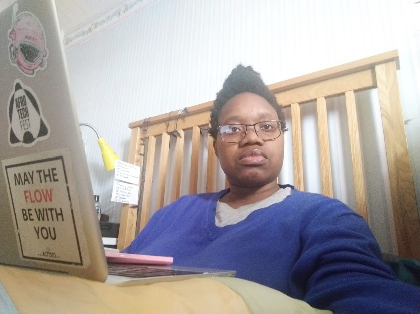 LILi is sat up in bed, facing the camera with a neutral expression, propped on their lap is a laptop and notebook on a cushion. That laptop has Afrotech Fest stickers and a sticker that reads 'may the FLOW be with you'. In the background in a lamp and some index cards fixed to the bed.