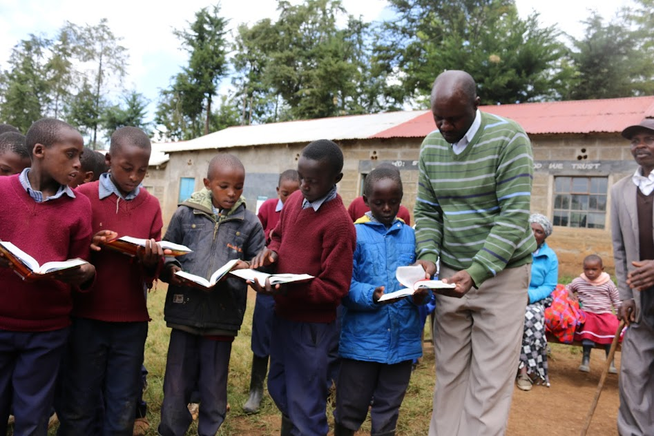 Displaying MEKARO PS DEPUTY HEAD TEACHER HELPING PUPILS OUT WITH OPENING A BIBLE VERSE.JPG
