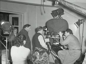 """Photo: Mikhail Kalatozov (de costas, ao centro) e o diretor de fotografia Serguei Urusevski (olhando pelo visor da câmera) durante as filmegens de""""Quando voam as cegonhas""""."""