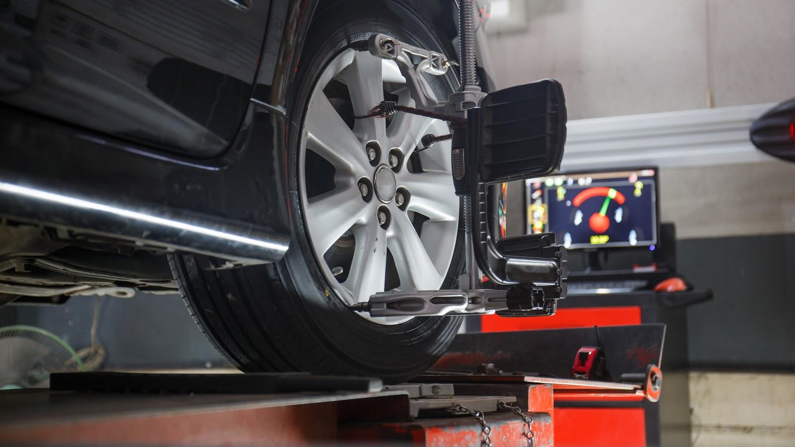 Car going through wheel alignment checks in a professional garage.