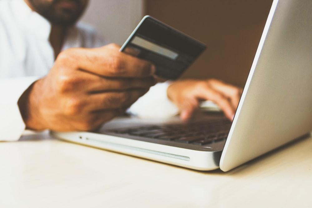 Persona usando un ordenador con una tarjeta de crédito en la mano