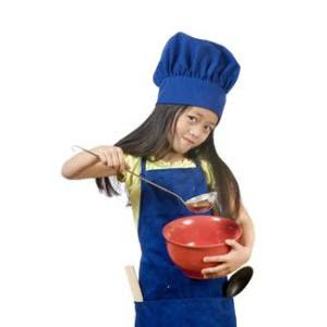 little girl wearing chef's hat and holding bowl and ladle