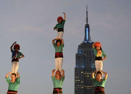 """Photo: Des """"Castellers de Vilafranca"""" forment des tours humaines pour battre un nouveau record du monde, avec la première tour de huit étages jamais réalisée sur un toit d'immeuble à New York. (© 2012 AFP)"""