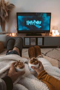 Couple sitting at home, watching a Harry Potter movie, and having dessert.