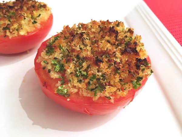 Two Tomato Halves With Stuffing On A White Plate.