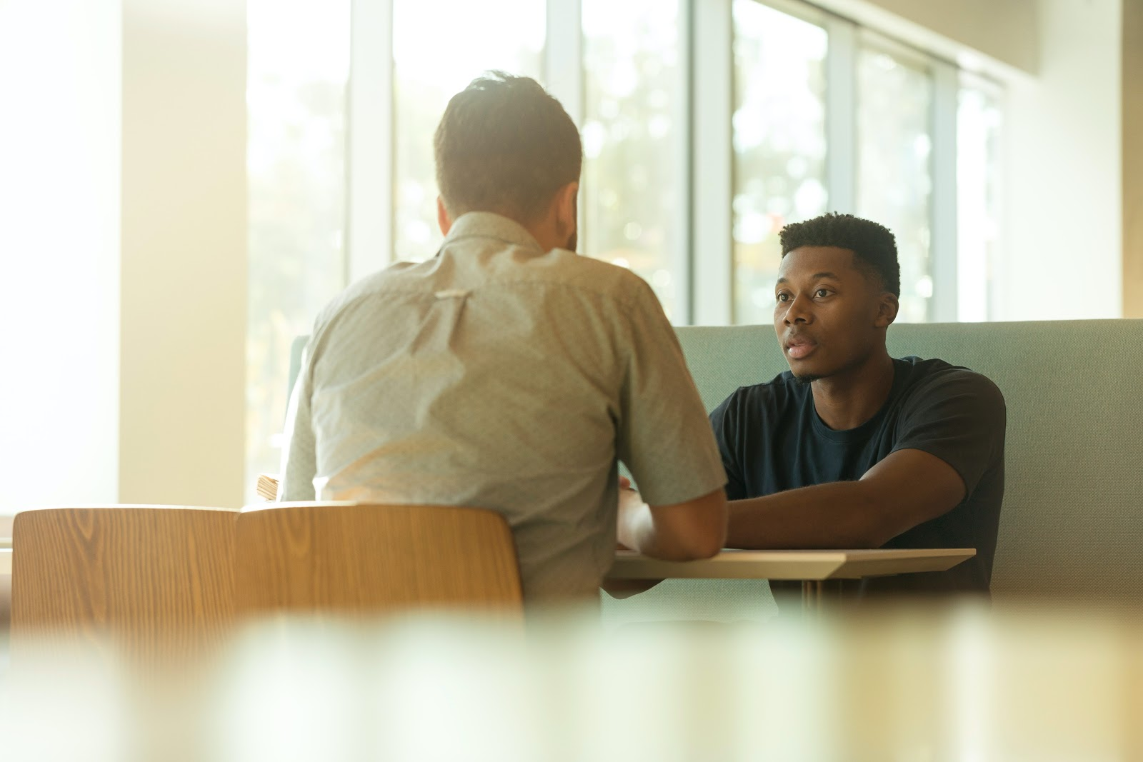 Dois homens conversando em uma mesa.