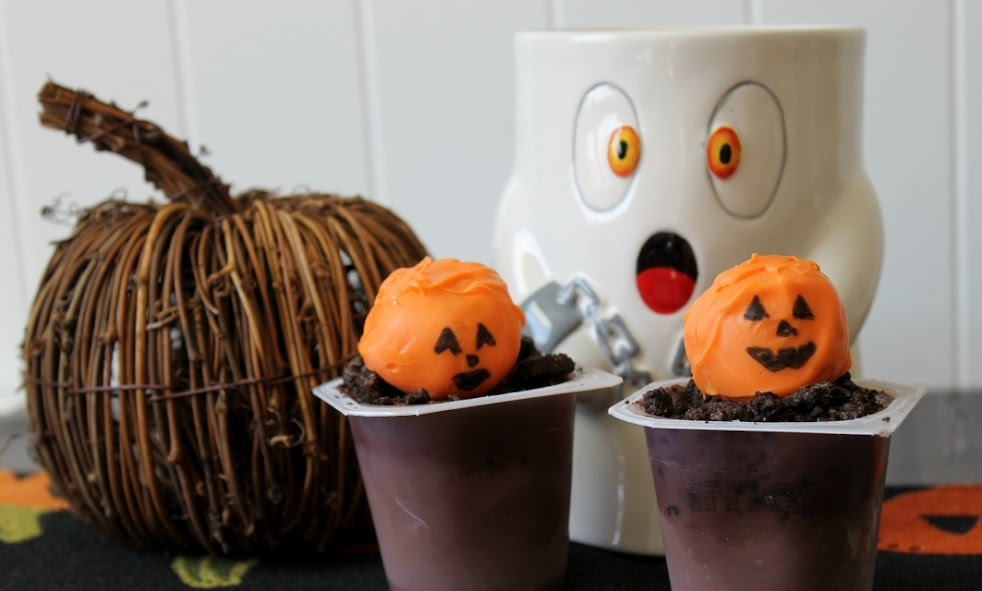 These fun Headless Horseman Graveyard Halloween treats are made with peanut butter ball jack o'lanterns, crushed chocolate cookies, and Snack Pack pudding cups