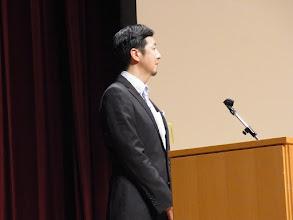 Photo: 座長から紹介される山崎先生