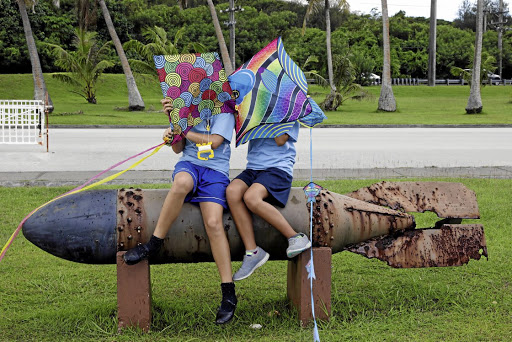 Children sit astride a Second World War torpedo at Asan Memorial Park on the island of Guam. Picture: REUTERS