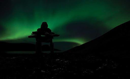 The Northern Lights seen against the silhouette of a rock edifice built by the native Inukshuk at Torngats Mountains in Newfoundland and Labrador Province.