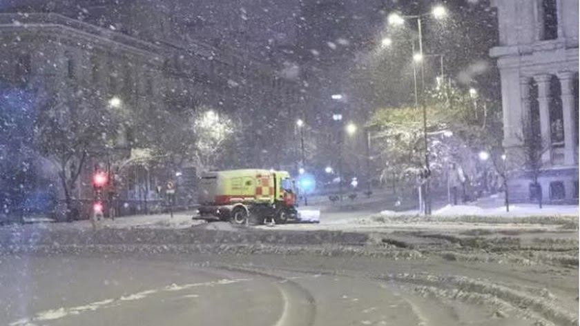Una máquina quitanieves pasa junto al Ayuntamiento de Madrid, cubierto de nieve por la borrasca Filomena.