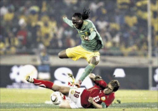 South Africa's Reneilwe Letsholonyane (TOP) avoids a tackle from Bulgaria's Stiliyan Petrov during their international friendly soccer match at Orlando stadium in Soweto, May 24, 2010.  REUTERS/Siphiwe Sibeko (SOUTH AFRICA - Tags: SPORT SOCCER WORLD CUP IMAGES OF THE DAY)