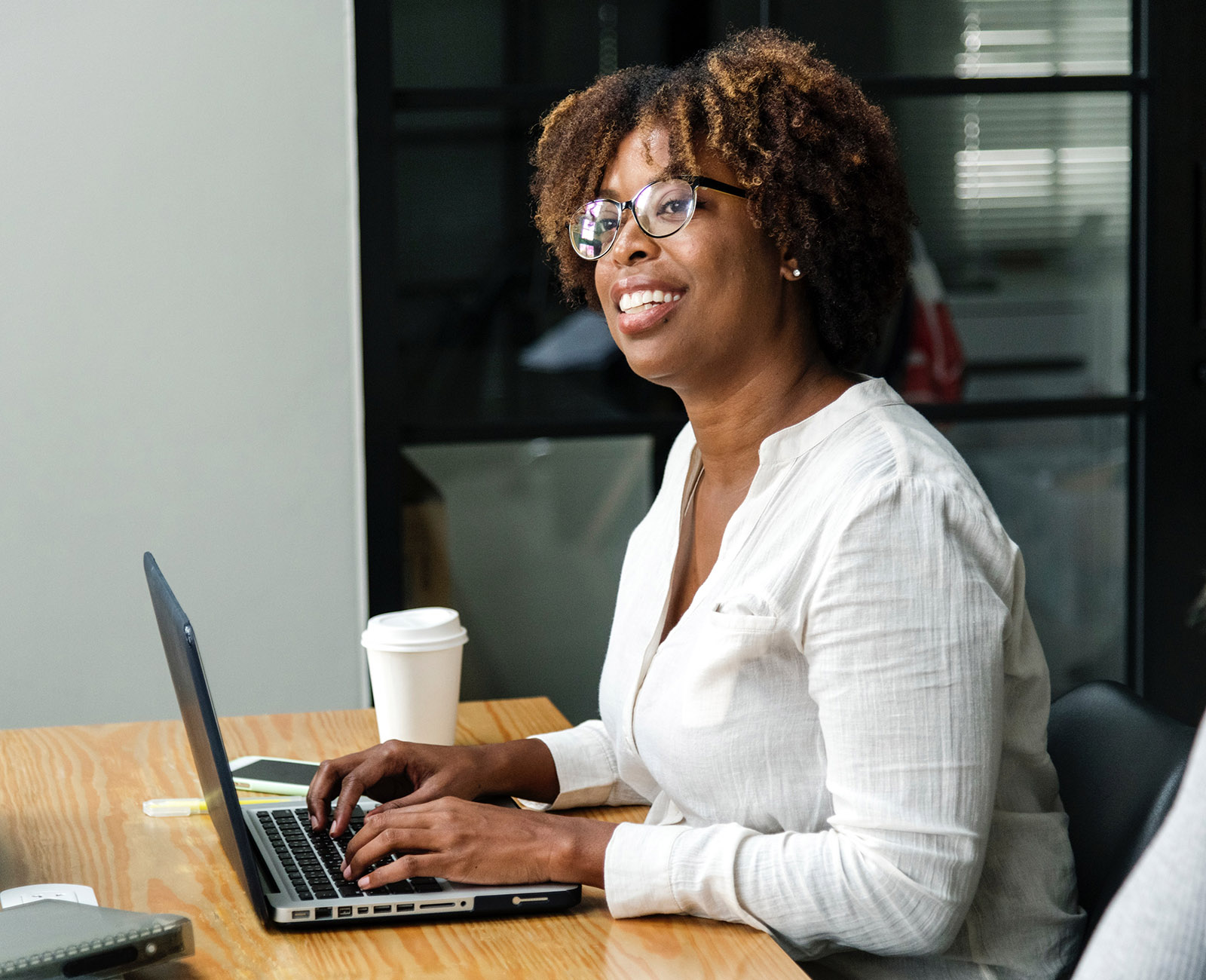 Female-identifying coder at laptop smiling, with coffee