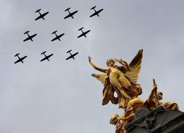 Vintage military aircraft perform a fly past over the Queen Victoria Memorial and Buckingham Palace to mark the centenary of the Royal Air Force in central London.