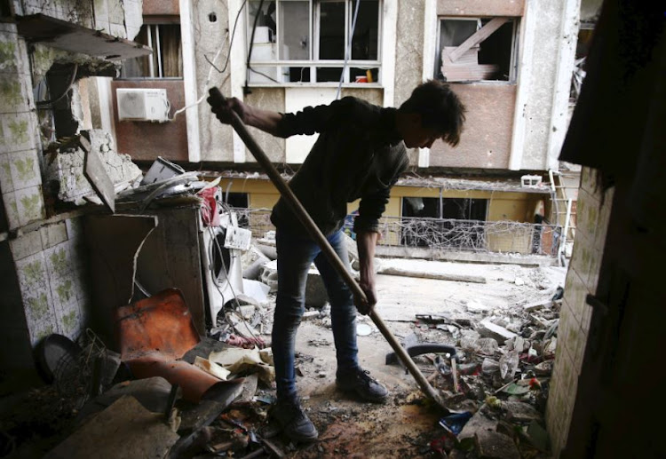 A young man cleans a damaged house in the besieged town of Douma, Eastern Ghouta, Damascus, Syria February 25, 2018.