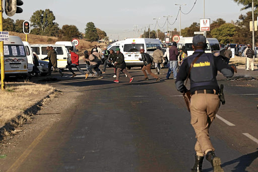 Taxi drivers flee as the Tshwane Metro Police, the SAPS and SANDF soldiers acted on the drivers who had blockaded the R55 in Laudium, Pretoria, yesterday, preventing people from going to work during a strike over government relief fund./Thuulani Mbele
