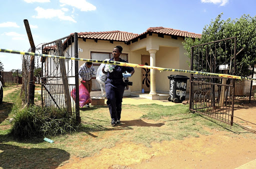 A forensic pathology team at the crime scene at a house in Vlakfontein where seven people were found dead.