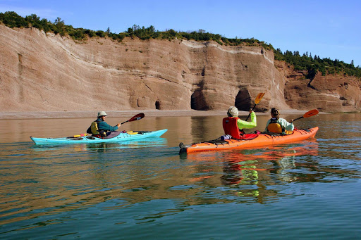 Kayakers explore the St. Martins Sea Caves, 25 miles east of St. John on the Bay of Fundy in Atlantic Canada.