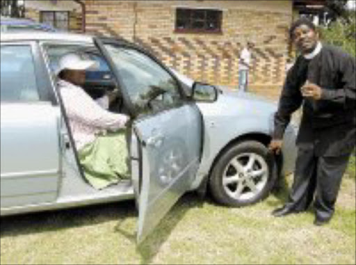 PROTECTION: Reverend Mlawuli Mayekiso blessing the car of Sheila Meko during a special ceremony, a first of its kind, of blessing cars at the African Methodist Episcopal Church in White City Jabavu in Soweto on Saturday. Pic. Munyadziwa Nemutudi. 03/02/08. © Sowetan.