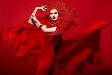 vrouw in rood en wijd waaiende rode cape tegen rode achtergrond
