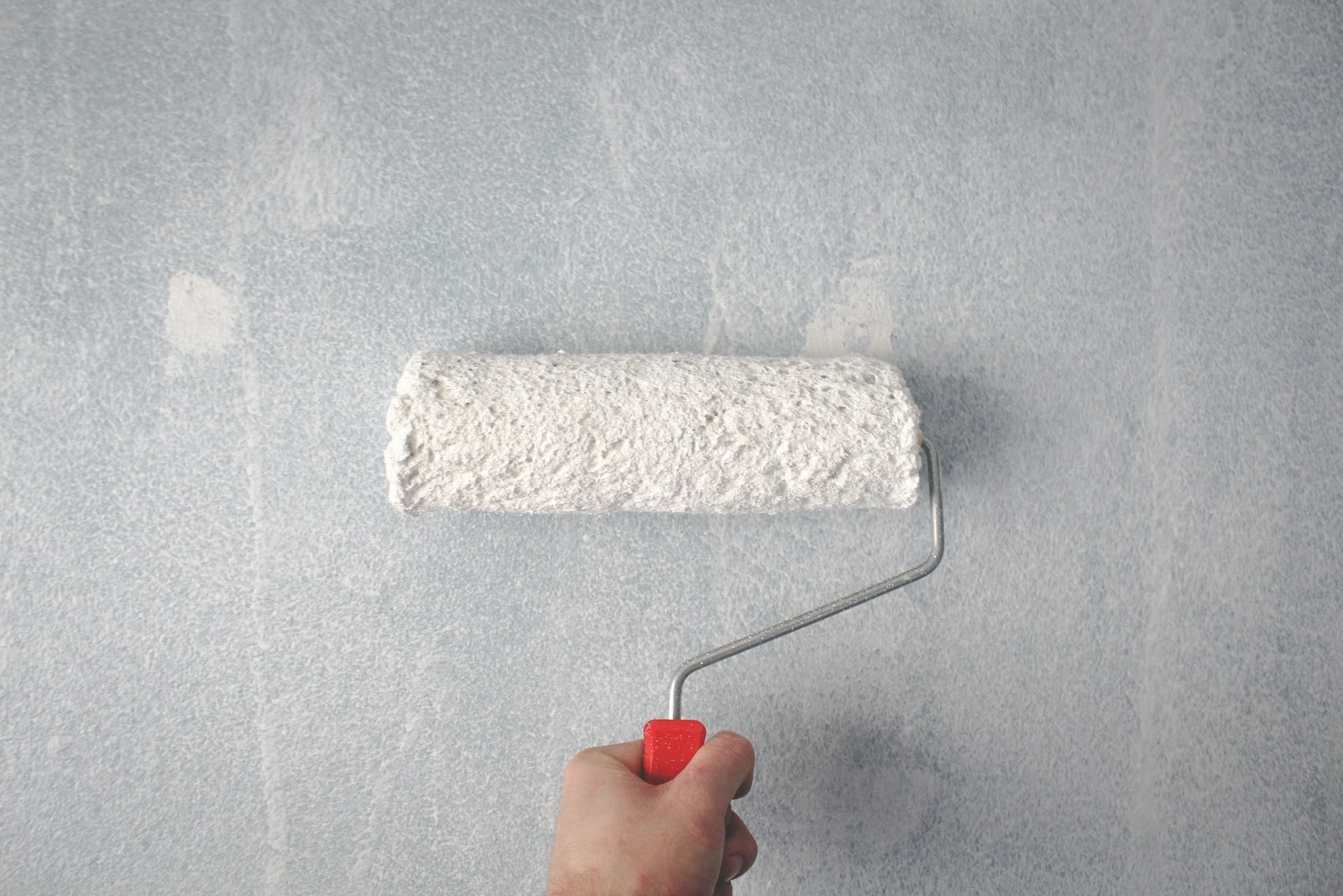 Paint roller painting white paint on to a wall.