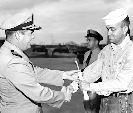 Photo: Executive Officer CDR F.O. Green, presents a Fire Axe to Perry Murphy, AB2, section leader of the outstanding crash crew section for the month of December, 1958