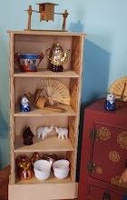 """Photo: Top of the book shelf:  Hand carving.  First shelf: A bowl found at Good Will and the tea pot is a trinket box.  Upper middle shelf: Cheap glass panda, bamboo fan from the craft store and another wooden carving.  Lower middle shelf: Mini Buddha from an import store and cheap glass elephants.  Bottom shelf: The doll sized soup bowls are actually people sized tea cups from an import store and some """"copper pots"""" found at Good Will.  My dad made the book shelf."""